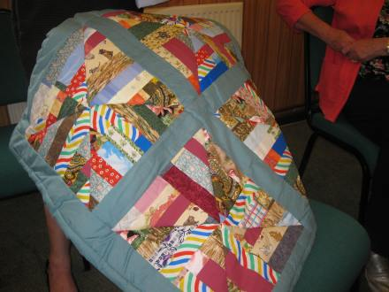 Patchwork quilt with multicoloured blocks on a blue background